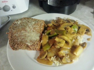Veggie stir-fry in spicy peanut sauce on a bed of brown rice, with a slice of homemade spelt bread.